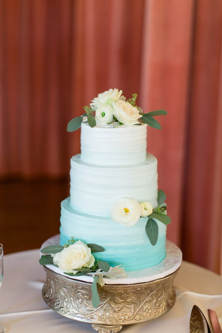 The Thursday Club Blue ombre beach wedding cake decorated with white ranunculus & roses by San Diego wedding florist, Compass Floral.