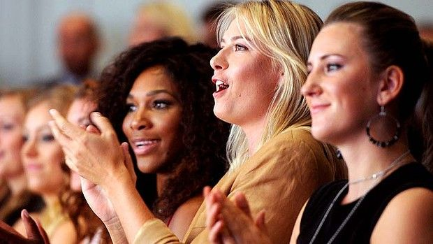 Fits and giggles ... Maria Sharapova of Russia and Serena Williams find it hard to concentrate on the ceremony.