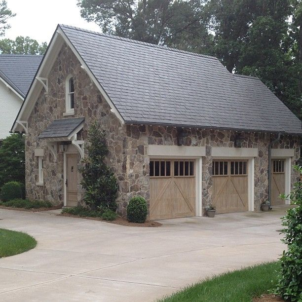 Stone garage with studio space above. Love the cerused doors too!