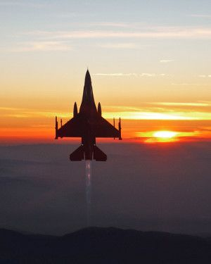 An American Air Force jet goes vertical in the late afternoon of setting sun