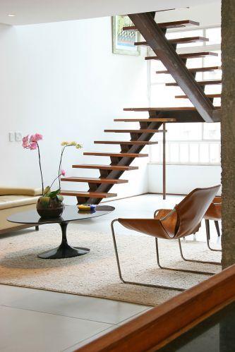 Escada metálica em U, com viga central e degraus em madeira. A autoria é do escritório FGMF Arquitetos