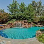 Bela piscina de hidromassagem tradicional com característica da água com plantio ao lado da piscina e pavers de pátio. -. Pool Waterfall Ideas   – Pool