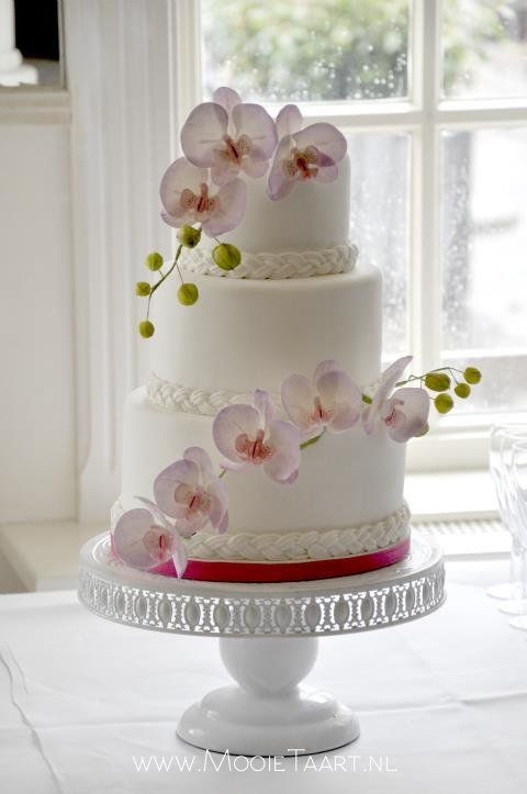 White wedding cake with branches of pink orchids on a rainy day ;-)