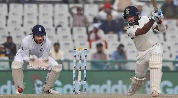 India's Cheteshwar Pujara plays a cover drive for a boundary as England's wicket-keeper Jonny Bairstow watches on the fourth day of their third cricket test match in Mohali, India, Tuesday, Nov. 29, 2016. (AP Photo/Altaf Qadri)