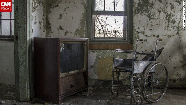 """Abandoned asylum. """"Forest Haven, Maryland. """"The dust on the TV and wheelchair shows how untouched parts of the hospital are and will remain,"""" Kina said."""