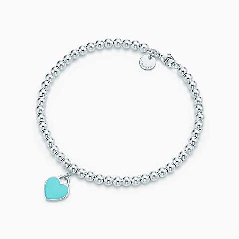 Berloque de coração mini em prata de lei em uma pulseira de contas.