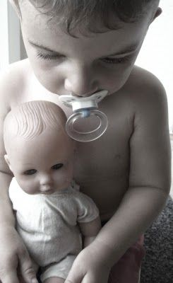 Kind nuckelt mit Puppe auf dem Schoß