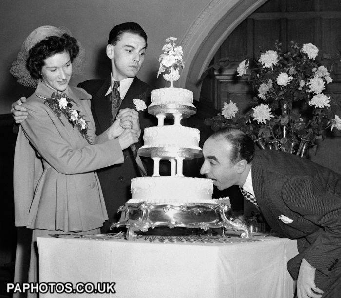 1949 - Radio comedian Bob Monkhouse and his bride Elizabeth Thompson, a former nurse from Belfast at their wedding reception at Caxton Hall, London. Harold Berens is taking a bite of their cake as they attempt to cut it.