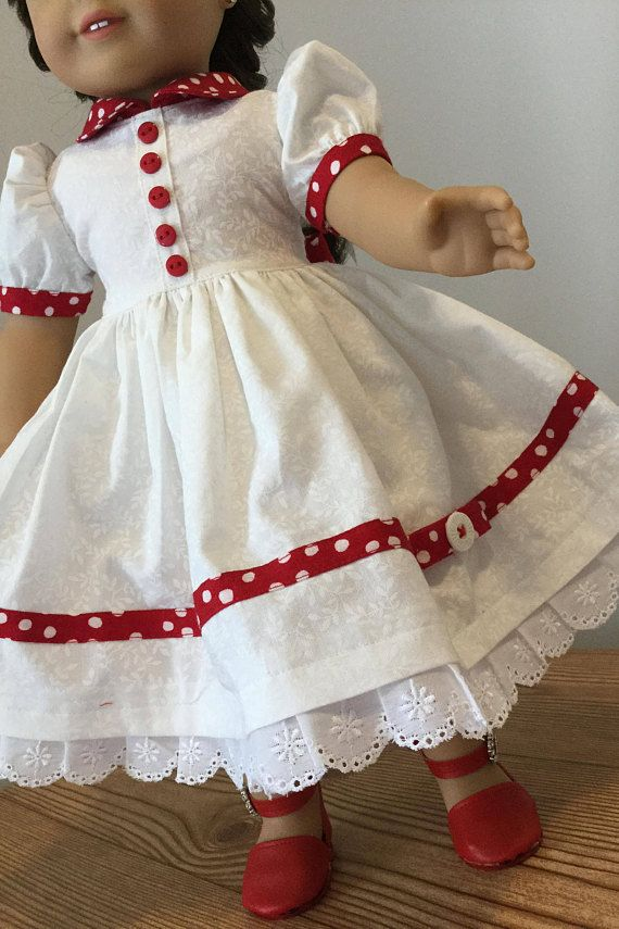 Lets Party white printed dress / red accents. This dress is a cute dress for mybe a Christmas party for your doll. It has a full gathered skirt in white printed cotton fabric, with a nice bright red accented bias around the lower skirt, with a bow and button attaced to the bias
