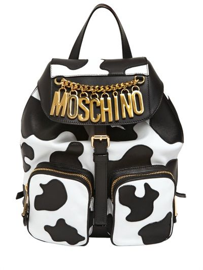MOSCHINO - COW MOTIF NAPPA LEATHER BACKPACK Height: 32cm   Width: 27cm   Depth: 12cm. Double adjustable padded leather shoulder strap. Single leather top handle. Front flap with buckle closure. Cow motif appliqués. Two front zip pockets. One internal zip pocket. Logo lettering . Gold color metal ha Trovato su Styletorch