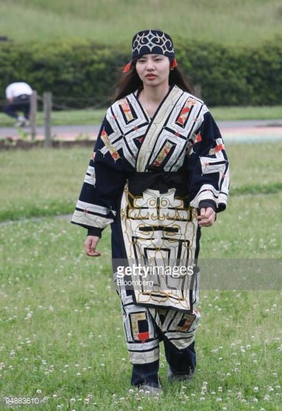 An Ainu woman in a traditional costume walks during a ritual ancestor worshipping ceremony on a river bed in Tokyo, Japan, on Sunday, April 8, 2008. Japanese lawmakers passed a resolution in...