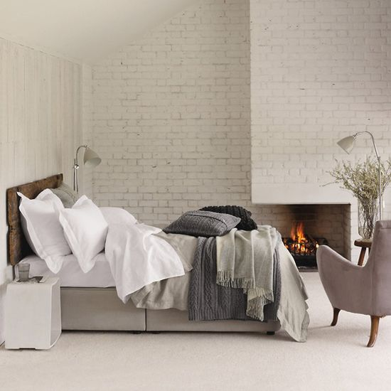 neutral texture bedroom, white brick fireplace + grey wood bed