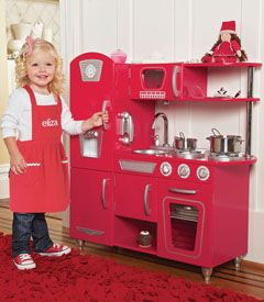 Red Retro Kitchen: Kids will be cooking up fun with this stylish kitchen set. Gourmet details abound -- doors open and close, knobs turn, the microwave and oven doors have windows, and the sink is removable for easy cleanup. There's even a cordless phone for pretend calls! (Cookware is sold seperately) Durable wood and plastic construction; lacquer finish.
