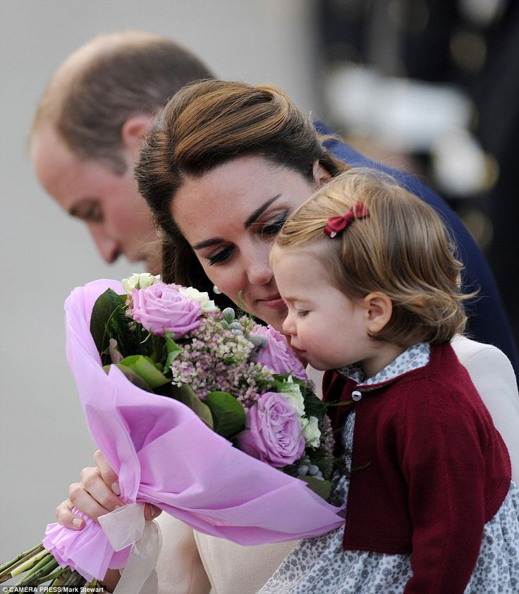 Charlotte smells a bouquet of flowers given to her mother as the family say their goodbyes to crowds and leave Canada