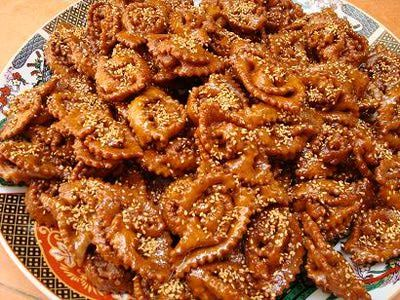 How to Make Chebakia - Mkharka (Moroccan Sesame and Honey Cookies)_(Halwa Chebakia, Shebakia)_is a Moroccan sesame cookie made by folding dough into a flower shape, frying it and then dipping it in hot honey flavored with orange flower water. The cookie is also known as mkharka.