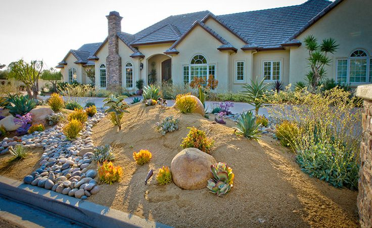 Medium sized boulders have among the desert plants give this xeriscape a organic style. https://ecomindedsolutions.com/project/front-and-backyard-poway-ca/