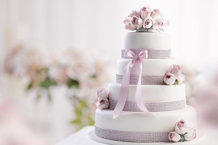 Svatební dort potažený bílým fondánem, dozdobený stuhou s kamínky a živými květinami. photo: Petr Vaněk design: KANTORS CREATIVE CLUB