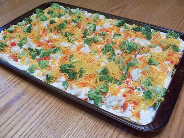 A classic veggie pizza recipe made with crescent roll dough, a mixture of cream cheese, sour cream, and ranch salad dressing, and topped with chopped vegetables and cheese. Serve this cold for brunch or as an appetizer. This is a quick and easy recipe that is a hit at family gatherings, parties, or bridal and…