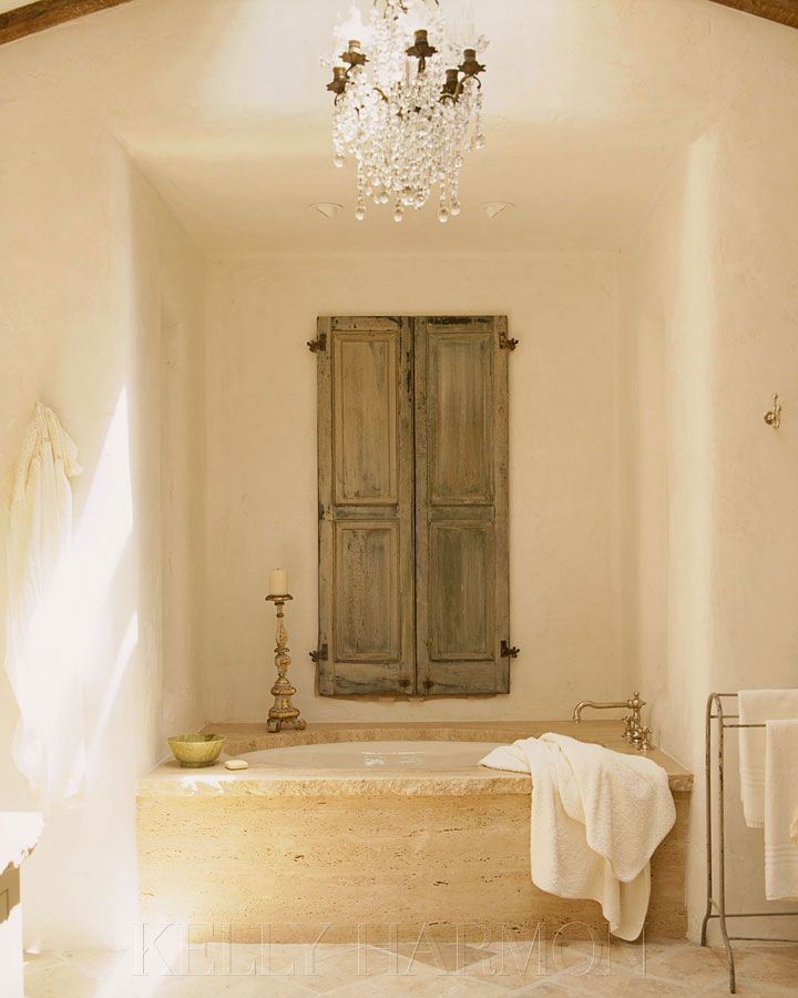 Travertine tub surround and antique French doors as shutters;
