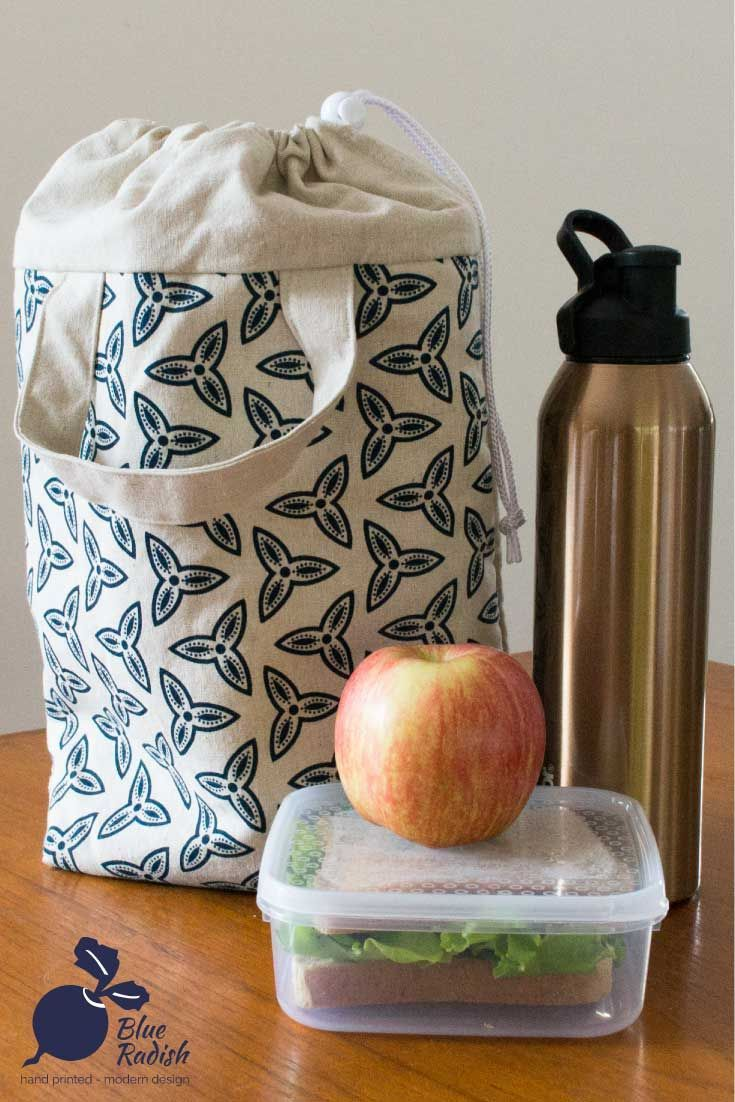 Insulated lunch tote with drawstring closure and waterproof food-safe lining. Trefoil design handprinted in navy ink onto natural linen-cotton fabric. The insulation has a foil layer to reflect heat and cold back into the bag.