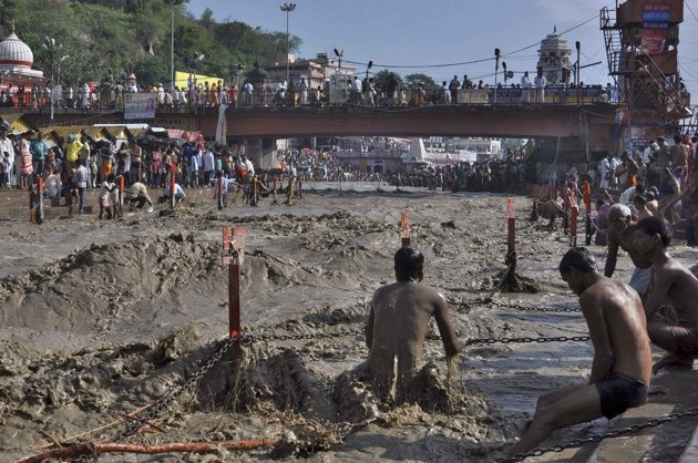 A devotee tries to take a holy dip in the flooded waters of river Ganges in the northern Indian town of Haridwar June 18, 2013. Early monsoon rains have swollen the Ganges, India's longest river, swept away houses, killed at least 60 people and left tens of thousands stranded