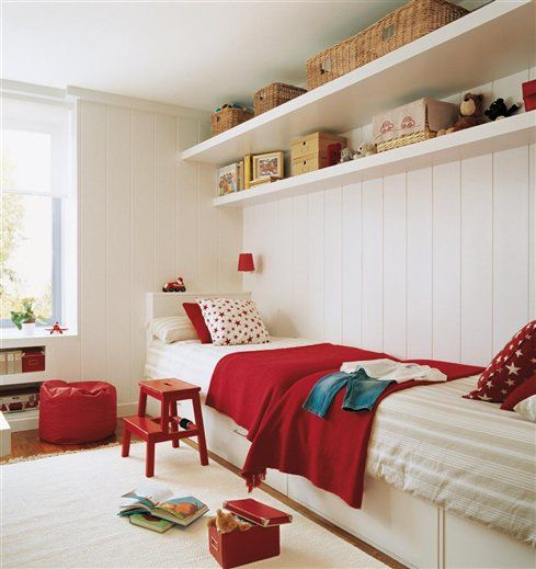beds against a long wall, red accents, storage shelves, and white planked walls.:
