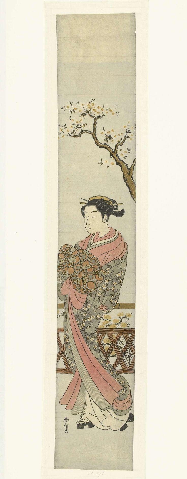 Suzuki Harunobu   Courtisane onder bloesemende boom, Suzuki Harunobu, 1765 - 1770   Courtisane in kimono met patroon van witte bloemetjes, paraderend onder bloesemende boom; bij hekje waarachter gele bloemen.