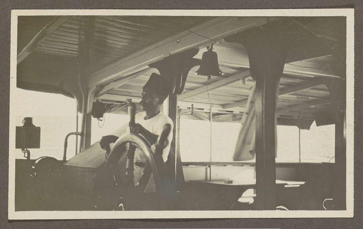 Anonymous | Indische man achter het stuurwiel van een schip, Anonymous, 1920 - 1930 | Onderdeel van Familiealbum Nederlands-Indië.