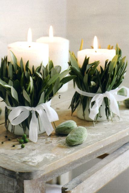 Chunky pillar candles tied with olive leaves and white ribbon to decorate an alter or mantlepiece via Kim's blog - Parisian Party (source:Marie Claire)