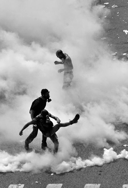 Protesters kick away tear gas fired by riot police during a 24-hours general strike in Athens, June 15, 2011.