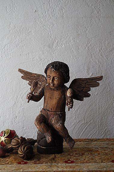 ヘーゼルアイの智天使-antique wood carved angel 褐色の肌をしているプットのオブジェ、榛色のガラスの眼、黒い髪に大人びたお顔はどことなくヒスパニックな趣き。奏楽の天使は黙示録のラッパ吹きやリュートを奏でる姿が主ですが、こちらのマラカス?の様なものはついぞ見かけた事がなく。背の高い柱に乗せ羽ばたく様に見上げるディスプレイも表情活きる、存在感のある木彫の天使。彩色が剥がれている箇所があり、握った指先に欠損が御座います。
