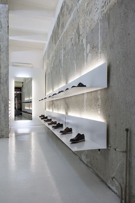 White shelves hang from concrete walls at shoe shop by Elia Nedkov