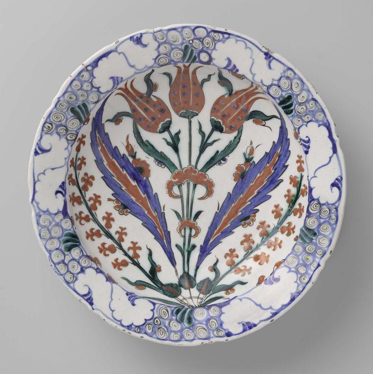 Anonymous | Plate with a Floral Motif, Anonymous, c. 1570 - c. 1590 | Kwarts-fritgoed met lood bord gedecoreerd met tulpen, bloemen in blauw, rood, groen, zwart op wit onder een transparant lood-alkali-tinglazuur.