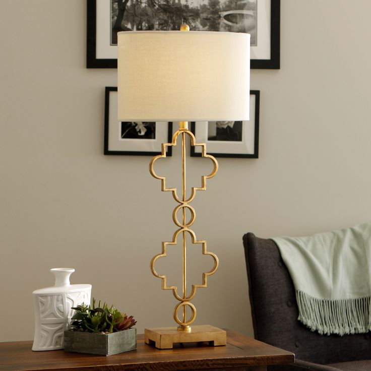Add a touch of sophisticated charm to any accent table with the Moroccan Table Lamp, showcasing a stunning antique gold leaf finish. This single-light fixture also offers contemporary styling with its white fabric shade.