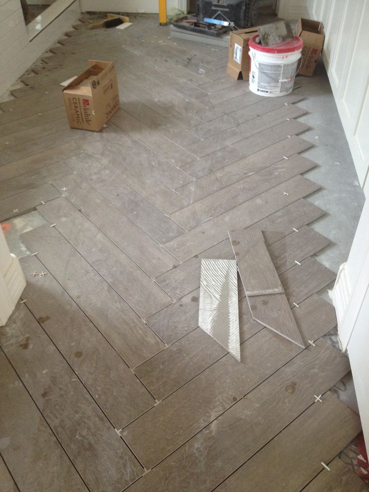 Bathroom floors, herringbone chevron pattern faux wood tile. Gray brown