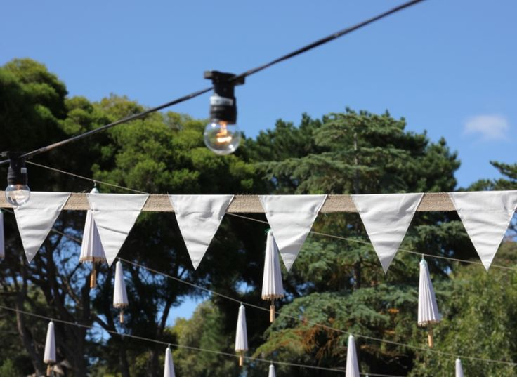 Outdoor lighting, bunting and pop up umbrellas for a gorgeous outdoor wedding event
