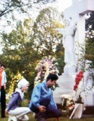 Elvis visiting his mother's grave in spring 1966 in Memphis with friends.