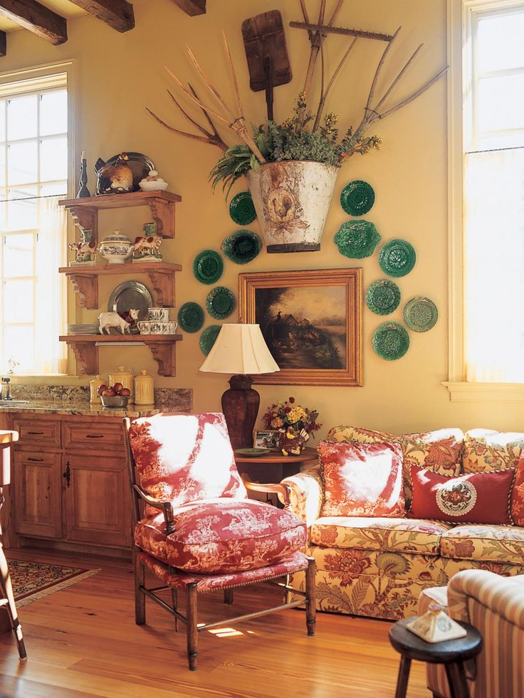 A floral loveseat and red armchair create a cozy sitting area in this Tuscan kitchen. A collection of green plates and platters surrounds a distressed bucket with various wood farming tools for an unusual but fitting wall decor piece.