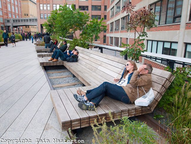 Cool bench for the backyard.  People relaxing on wooden benches at the new High Line elevated landscaped public walkway built on old railway viaduct in Chelsea district of Manhattan in New York City USA