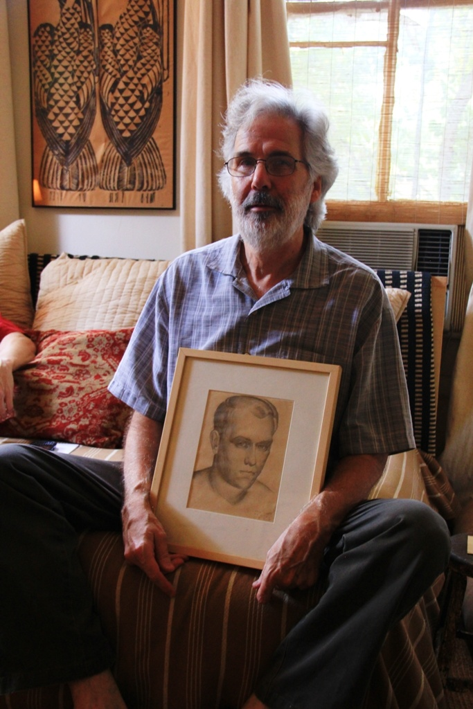 """The family tree of Mississippi artists is intricately woven. Here, artist Ron Lindsey (who is the subject of portraits by Wyatt Waters, Paul Fayard, and Tony DiFatta, and the painter of portraits of Paul Fayard and Tony DiFatta included in """"Artists by Artists""""), holds a self portrait of Karl Wolfe given to him as a gift by the Wolfes. Karl Wolfe was a contemporary of William Hollingsworth (whose life and work is on view in """"To Paint and Pray: The Art and Life of William R. Hollingsworth…"""