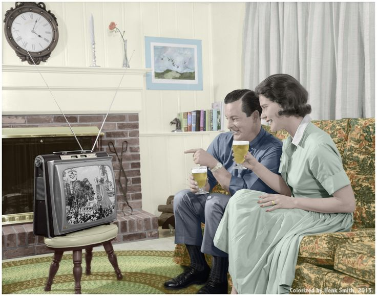 Circa 1960s: Smiling Young Couple Both Sitting On A Sofa With A Glass Of Beer In Their Hands Watching A Portable Tv Thats Sitting On A Stool In The Living Room. (Original Black And White Photo by H. Armstrong Roberts/Retrofile/Getty Images)