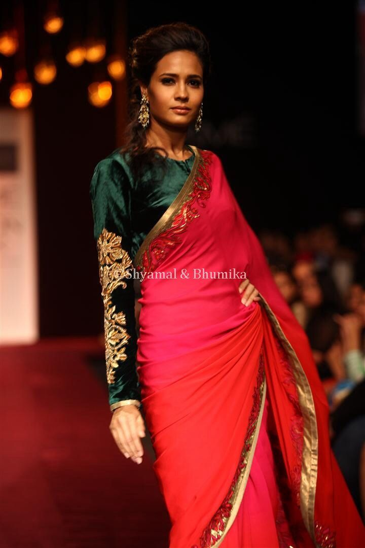 a scarlet red and fuschia pink ombre dyed saree with a unique mix of thread zardozi and metal sequins embroidery along the borders, with a emerald green velvet blouse with bold motifs on the sleeves.