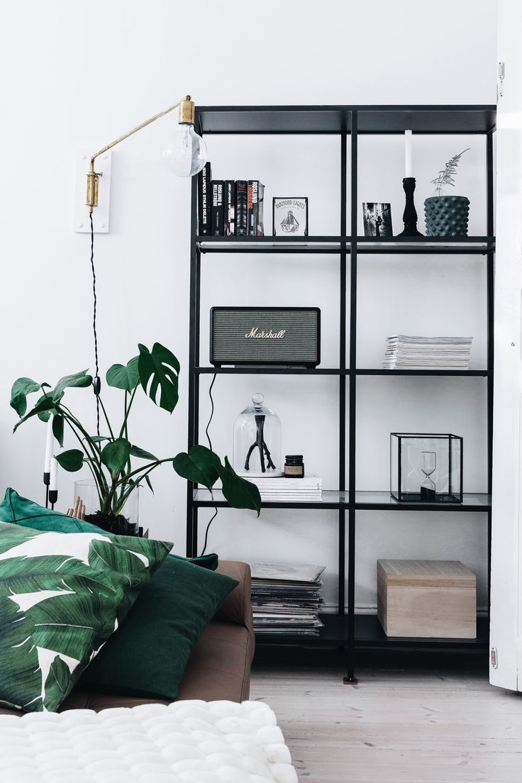The clean look of simple black metal shelving in a a green and tan living room.