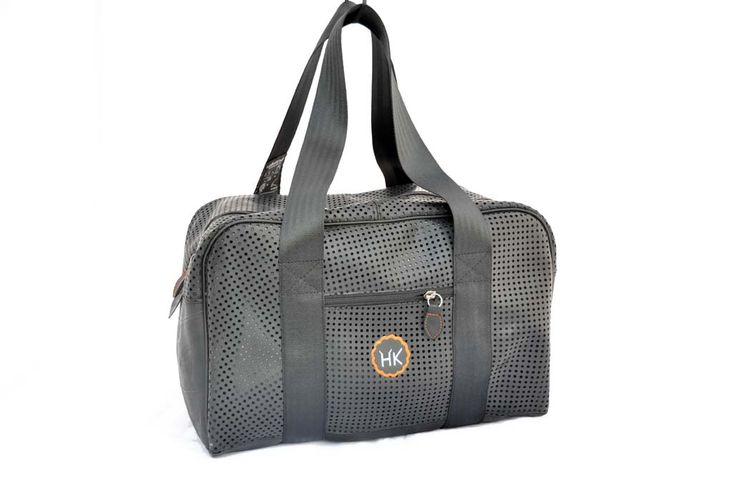 Sports bag made from perforated recycled inner-tube with central zip fastener. Medium-sized bag is ideal as hand luggage when travelling. Fully lined with a vintage shirt and with a small zip pocket. Large-size bag is unlined for more practical sports use. Handles made from used car seatbelts. All sizes have a small side zip pocket to keep small items within easy reach. By Hell's Kitchen.