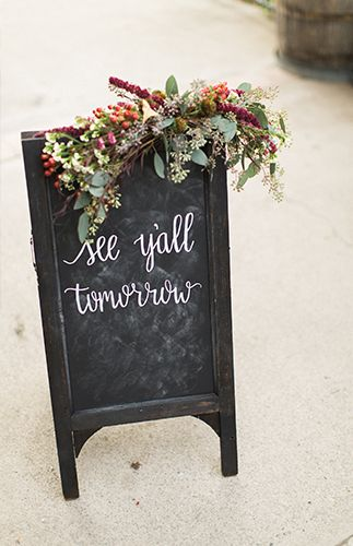 outdoor chalkboard wedding sign with floral swag | image via: inspired by this