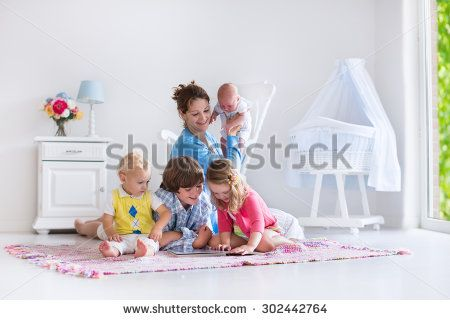 Mother and children play indoors. Family with kids in a white bedroom. Mom with baby, boy and girl playing and reading books at home. Beautiful nursery for baby and toddler. Room for preschool child.  - stock photo