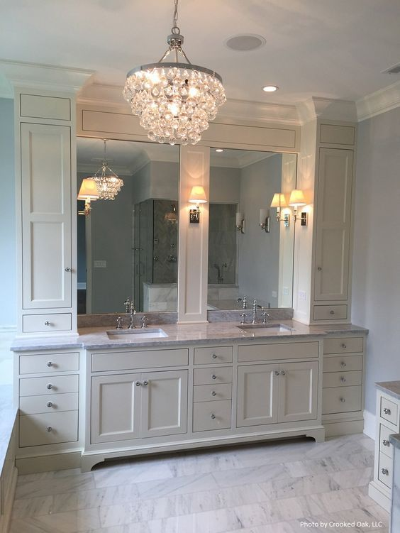 Website Picture Gallery Ivory master bathroom features a Robert Abbey Bling Chandelier illuminating ivory cabinets topped with gray marble fitted with his and hers sinks under
