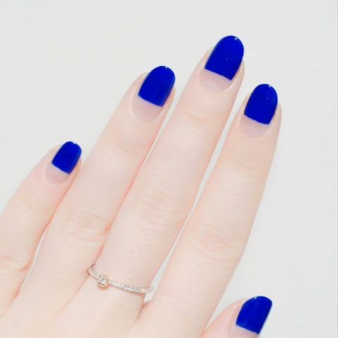 Keep the negative look minimal by taping off the base and painting your upper nail in solid royal blue. Design by @palemoonseattle