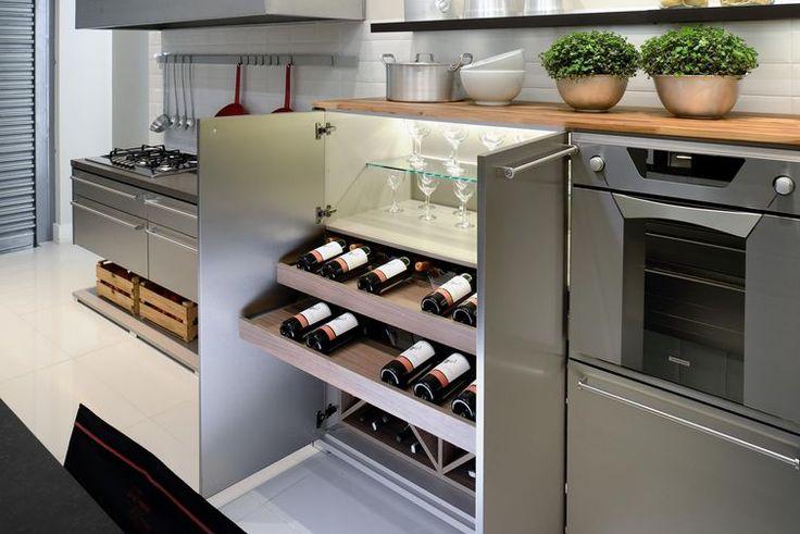 adega refrigerada embutida no armário. vinhos expostos em nichos em forma de X e também em prateleiras deslizantes
