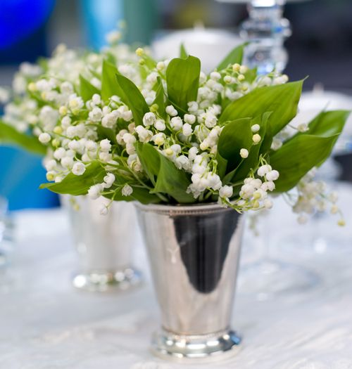 Lily of the Valley arranged in a tulip vase make for delicate-looking table florals for your wedding day.